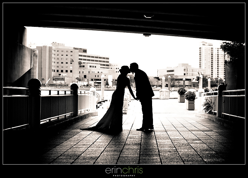 bride and groom kissing under a bridge on the tampa riverwalk